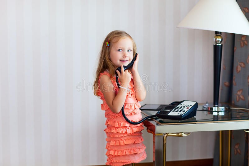 Little girl wearing a orange dress, talking on the phone and smiling
